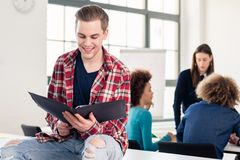 Portrait of a cheerful student holding an open folder in the classroom. Portrait of a cheerful handsome student holding an open folder while sitting on a desk Stock Photography