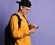 Portrait of a cheerful student wearing backpack, in cap and glasses and using smartphone over purple background royalty free stock photos