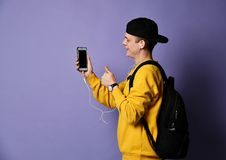 Portrait of a cheerful student wearing backpack, in cap and glasses and using smartphone over purple background royalty free stock photo