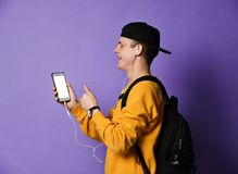Portrait of a cheerful student wearing backpack, in cap and glasses and using smartphone over purple background royalty free stock image