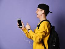 Portrait of a cheerful student wearing backpack, in cap and glasses and using smartphone over purple background stock images