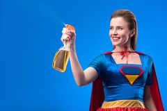 Portrait of cheerful superwoman with detergent in hand. Isolated on blue royalty free stock image