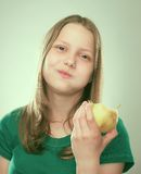 Portrait of a cheerful teen girl with an apple Stock Photos
