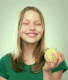 Portrait of a cheerful teen girl with an apple Royalty Free Stock Photo