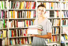 Portrait of cheerful teenager boy with book pile. In shop Royalty Free Stock Images