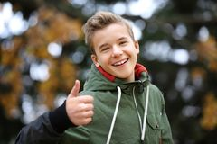 Portrait of cheerful teenager outdoors. On blurred background Royalty Free Stock Image