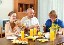 Portrait of cheerful three generations family eating  friuts wit Stock Photo
