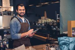 Beaming barista having job in cafe. Portrait of cheerful unshaven worker writing information while keeping clipboard in hand. He situating at counter in Royalty Free Stock Photos