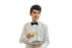 Portrait of a cheerful waiter in a white shirt with a glass of wine on a tray that. Is isolated on a white background close-up Royalty Free Stock Image