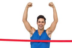 Portrait of cheerful winner athlete crossing finish line. With arms raised on white background Royalty Free Stock Images