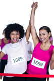 Portrait of cheerful winner athletes crossing finish line with arms raised Stock Photo