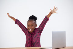 Portrait of cheerful woman with arms raised by laptop. At desk in office Stock Photos