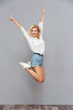 Portrait of a cheerful woman jumping and showing v gesture. Full length portrait of a cheerful woman jumping and showing v gesture isolated on a gray background Stock Photography
