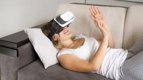 Portrait of young cheerful woman lying with VR headset on sofa and trying to catch something. Portrait of cheerful woman lying with VR headset on sofa and trying Royalty Free Stock Images