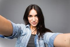 Portrait of a cheerful young woman making selfie photo over gray background. Portrait of a cheerful woman making selfie photo over gray background stock photography