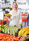 Portrait of cheerful woman offering fruits Stock Photo
