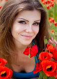 Portrait of cheerful woman outdoor with red poppy flowers in her hands Royalty Free Stock Photography