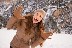 Portrait of cheerful woman outdoors among snow-capped mountains Stock Photo