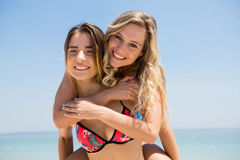 Portrait of cheerful woman piggybacking female friend against clear sky. Portrait of cheerful woman piggybacking female friend while standing at beach Royalty Free Stock Photography