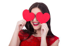 Portrait of cheerful woman in red dress covering eyes with two p Royalty Free Stock Images