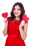 Portrait of cheerful woman in red dress holding two paper hearts Royalty Free Stock Image