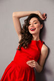 Portrait of a cheerful woman in red dress. Posing over gray background Royalty Free Stock Photography