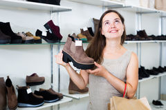 Portrait of cheerful woman selecting loafers. In footgear center Royalty Free Stock Image