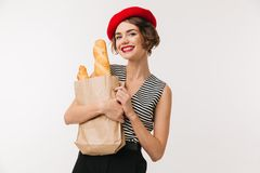 Portrait of a cheerful woman wearing beret. Holding paper bag with long loaf isolated over white background Stock Image