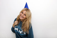 Portrait of cheerful woman wearing party hat against white background Stock Photos