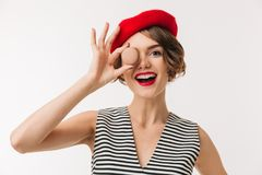 Portrait of a cheerful woman wearing red beret. Holding cookie at her face isolated over white background Royalty Free Stock Photos