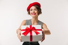 Portrait of a cheerful woman wearing red beret. Holding present box isolated over white background Stock Photography