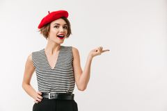 Portrait of a cheerful woman wearing red beret pointing. Finger away isolated over white background Royalty Free Stock Photos