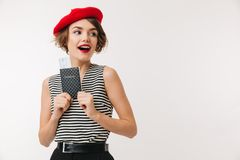 Portrait of a cheerful woman wearing red beret. Holding passport and looking away isolated over white background Stock Photo