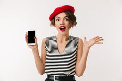 Portrait of a cheerful woman wearing red beret. Showing blank screen mobile phone isolated over white background Stock Photography