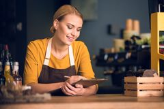 Outgoing female barista writing on paper. Portrait of cheerful woman worker noting information while resting elbows on table in cozy cafe. Occupation concept Stock Image