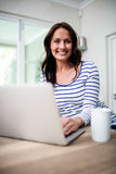 Portrait of cheerful woman working on laptop while holding coffee mug Royalty Free Stock Image