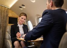 Successful colleagues enjoying their work. Portrait of cheerful women and her companion sitting in airplane seats at tray table opposite each other. Focus on royalty free stock image