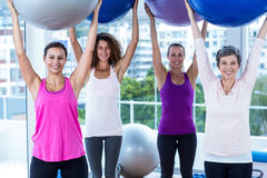 Portrait of cheerful women holding exercise balls with arms raised Stock Photography