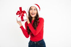 Portrait of a cheerful wondering asian woman. Dressed in red santa hat holding gift box and looking away at copy space isolated over white background Stock Photography