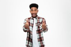 Portrait of a cheerful young african man. Dressed in plaid shirt showing two thumbs up isolated over white background Royalty Free Stock Photo