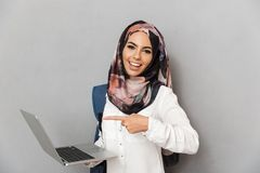 Portrait of a cheerful young arabian woman student. With backpack pointing finger at laptop computer isolated over gray background Royalty Free Stock Photos