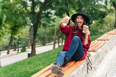 Portrait of a cheerful young asian girl dressed in hat. And sweater holding coffee cup while sitting on a bench and taking a selfie outdoors Stock Photos