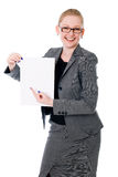 Portrait of cheerful young business woman holding a white blank. Banner. Isolated on white Stock Photography