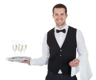 Portrait of a cheerful young butler. Portrait of a young butler with champagne glass. Isolated on white royalty free stock image