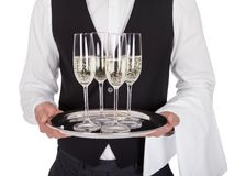 Portrait of a cheerful young butler. Portrait of a young butler with champagne glass. Isolated on white royalty free stock images