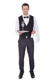 Portrait of a cheerful young butler. Portrait of a young butler with champagne glass. Isolated on white stock image
