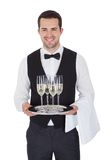 Portrait of a cheerful young butler. Portrait of a young butler with champagne glass. Isolated on white royalty free stock photography