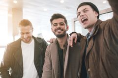 Glad friends expessing positive emotions. Portrait of cheerful young comrades standing indoor. Conversation and fellowship concept Royalty Free Stock Photos