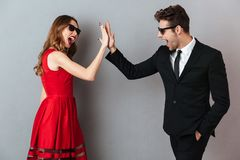 Portrait of a cheerful young couple dressed in formal wear. And sunglasses standing and giving high five over gray wall background Stock Image