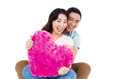 Portrait of cheerful young couple with heart shape pillow Stock Photo